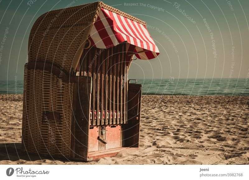 All alone and locked it stands there on the beach in the sand - the beach chair with a red and white sunshade Beach chair Ocean Sand on one's own beach sand