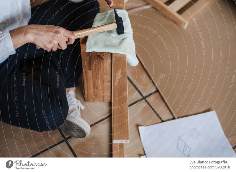 close up of young woman assembling furniture at home working with hammer. DIY concept do it yourself house caucasian indoor renovation young adult craft