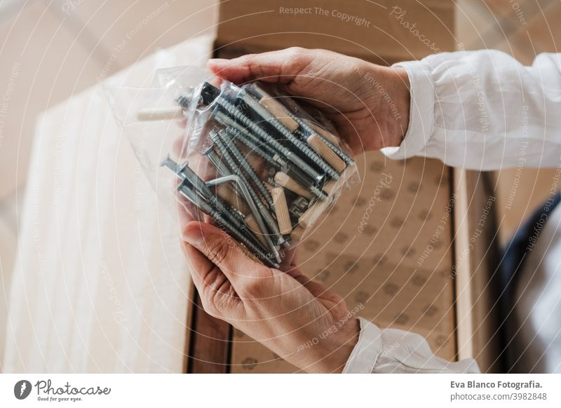 close up of young woman assembling furniture at home working with screws and nuts. DIY concept do it yourself house caucasian indoor renovation young adult