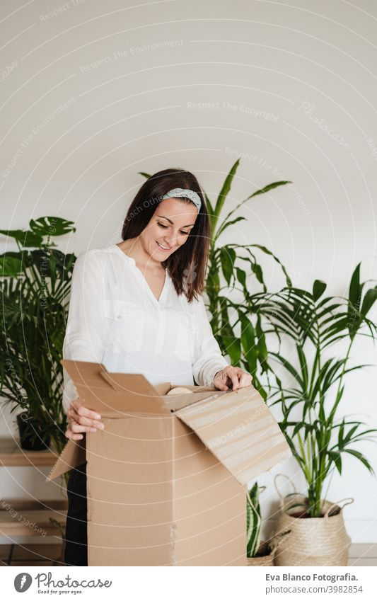 close up of young woman assembling furniture. Unboxing pieces from carton box. DIY concept do it yourself home house caucasian indoor working renovation
