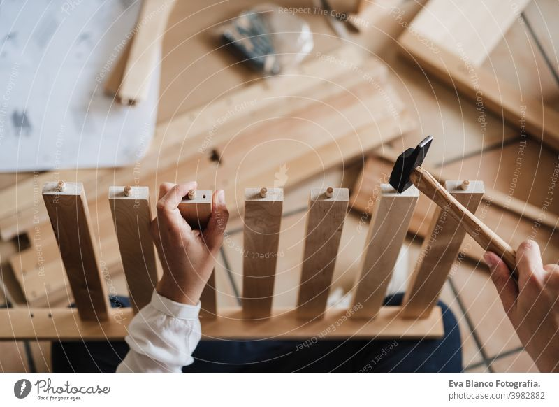close up of young woman assembling furniture at home working with hammer. DIY concept. top view do it yourself house caucasian indoor renovation young adult