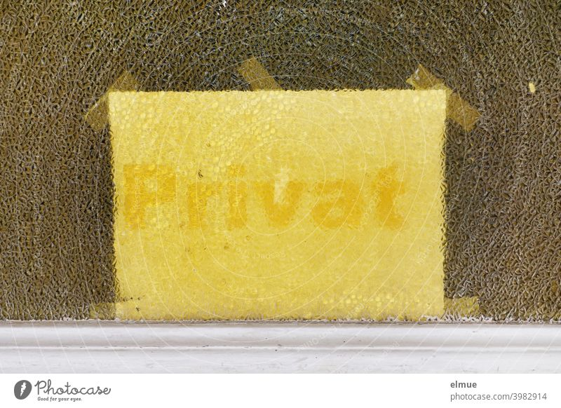 """Behind the textured glass pane of a door, a light yellow note with yellow writing """"Private"""" was attached by means of several adhesive strips / Privacy"""