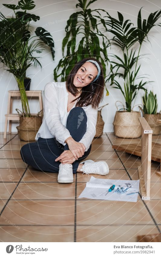 happy woman relaxing at home after working assembling furniture. DIY concept. do it yourself house caucasian indoor renovation young adult craft bricolage skill