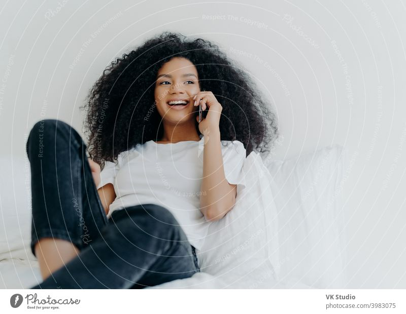 Pleasant looking curly woman has pleasant conversation, talks with friend via smartphone while relaxes in bed, has joyful expression, looks aside, wears casual clothing. People, bedding, technology