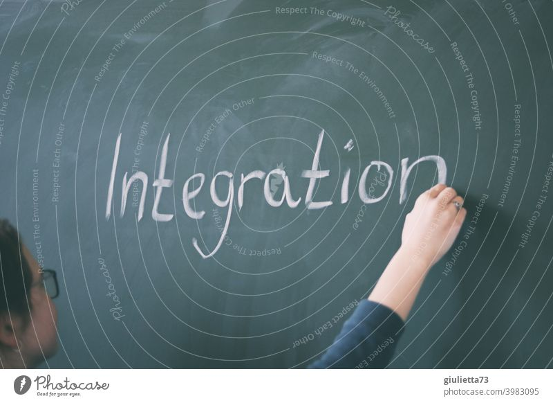 Young teacher writes the word integration on the blackboard with chalk 18-25 years Lessons Day Central perspective Woman Colour photo Green Education Study