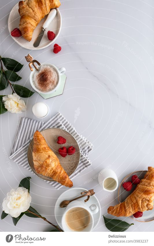 View from above of a breakfast table with croissants, coffee, raspberries, blood orange, boiled egg and flowers on a white wooden table, on white marble surface