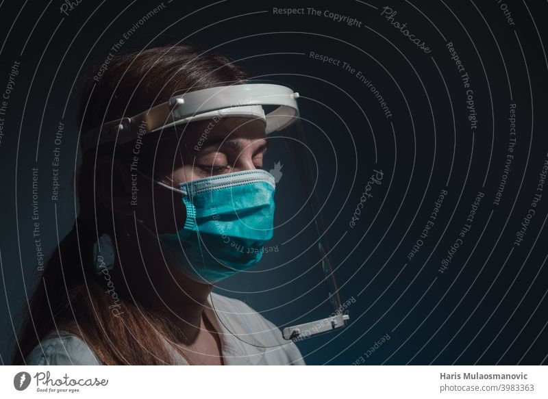 female doctor with face shield and mask, closed eyes, side view on dark background black background corona epidemic corona virus covid-19 covid-19 test