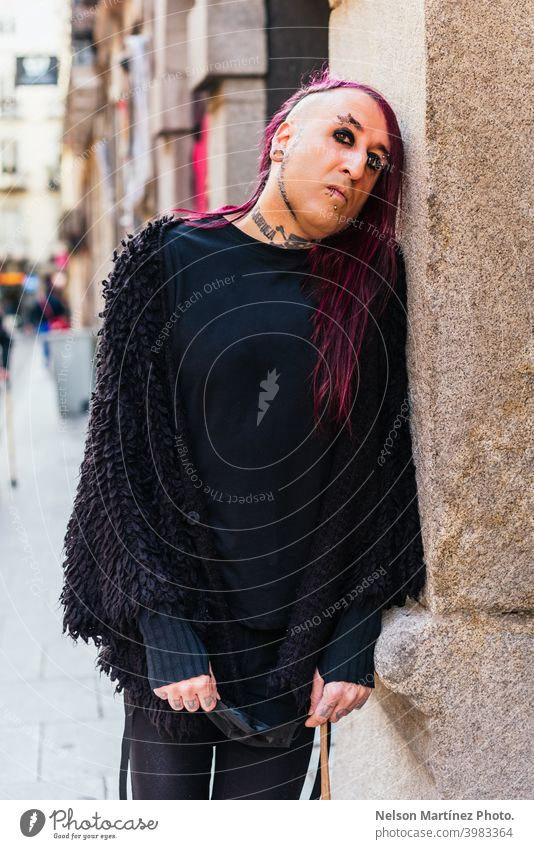 Portrait of an eccentric rocker wearing black clothes. He has tattoos and long purple hair. androgynous male beautiful young man feminine guy closeup gay
