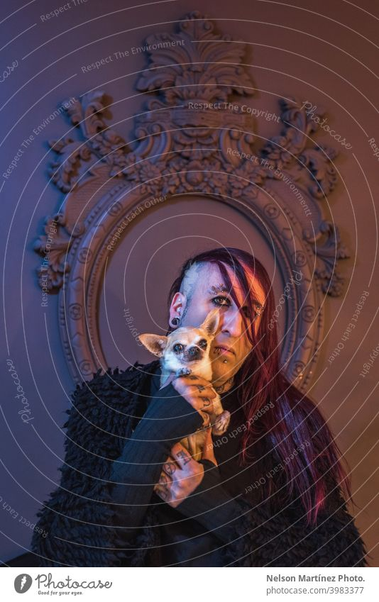 Framed portrait of an eccentric rocker with his little dog. He has long purple hair. androgynous male beautiful young man feminine guy closeup gay photogenic