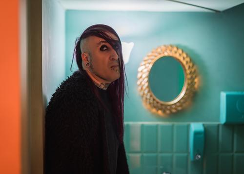 Portrait of an eccentric rocker man with long purple hair in a green bathroom. androgynous male beautiful young feminine guy closeup gay photogenic adult model