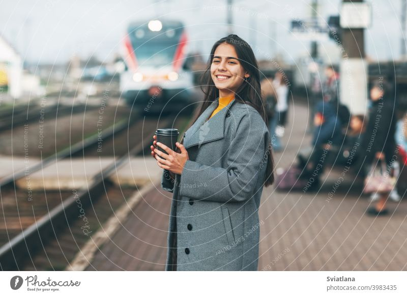 Happy girl enters the train at the station with coffee in her hands. transport young female beautiful railway passenger metro woman smiling public waiting