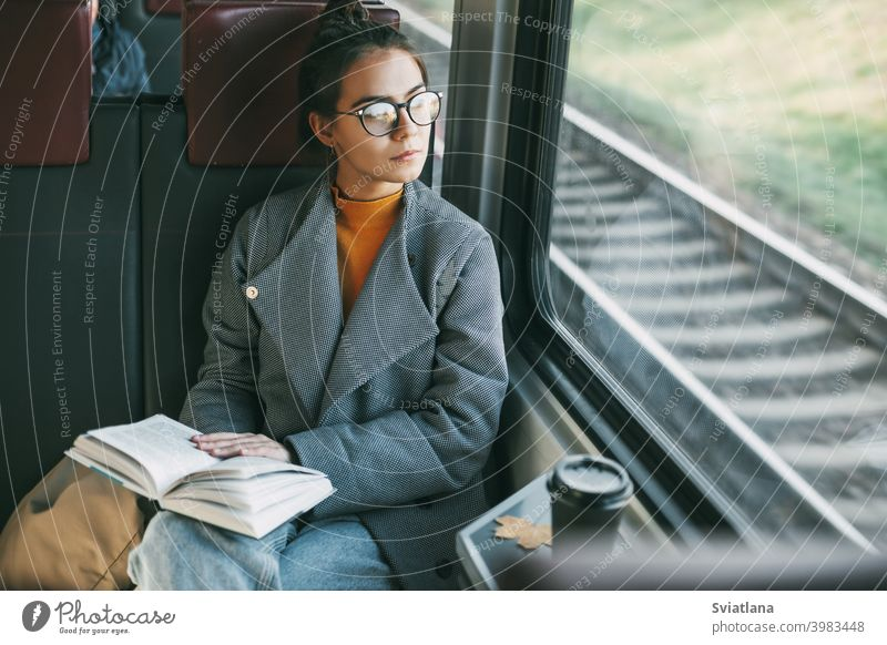 Young beautiful girl on a train reading a book while traveling in a train passenger happy journey coffee tourist calmness inside transport young sitting trip