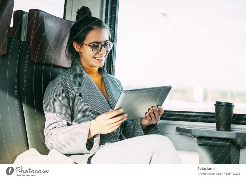 Young girl on the train communicating on the tablet with friends and relatives while traveling on the train woman passenger happy reading ebook inside online