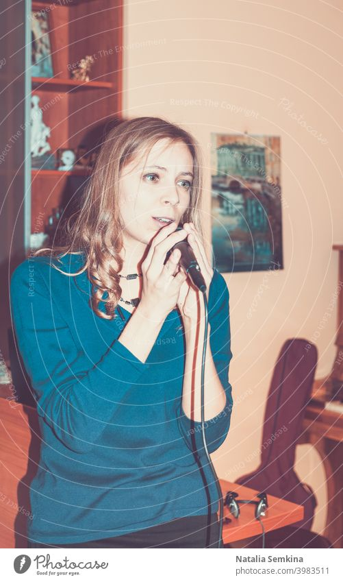 Young girl singing into a microphone at home. Retro toned image. 20s 25-29 years Waist Up adult attractive beautiful beauty cute feelingly female front hair