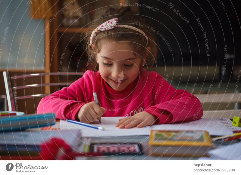 Smiling 6 year old girl does her homework child smiling write writing table case colors pens learning study schoolgirl desk childhood lesson student studying