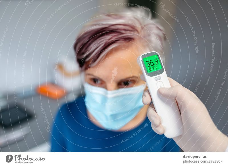 Senior woman without fever whose temperature is taken with an infrared thermometer senior no fever non-contact thermometer doctor covid-19 healthy checking