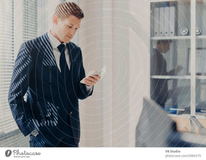 Concentrated male boss, keeps hand in pocket, focused into screen of smart phone, searches useful information for new startup, poses in office, dressed elegantly. Man chats on cellular at cabinet