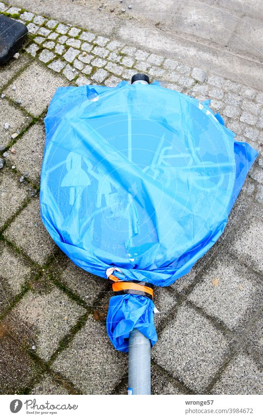 A traffic sign (traffic sign no. 241-31) covered with a blue transparent garbage bag is lying on grey cobblestone pavement Road sign footpath and cycleway