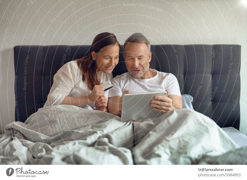 Happy middle-aged couple sitting in bed in the morning drinking coffee and doing online shopping with a digital tablet sofa furniture family room reclining