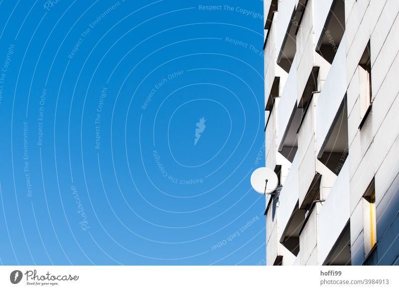lonely satellite antenna on a skyscraper facade Satellite dish High-rise facade Urbanization Isolation dreariness Facade Blue Blue sky Modern