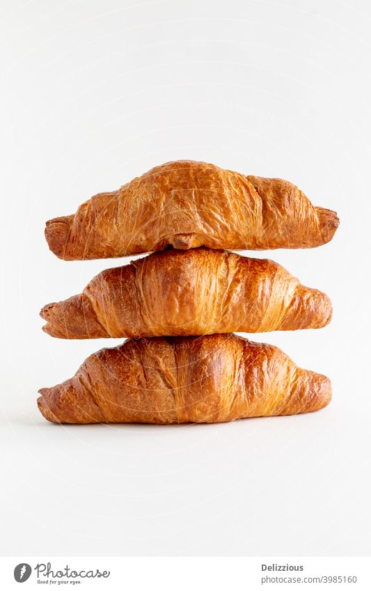 Three freshly baked croissants stacked on top of each other on a white background with copy space, close up baked pastry item bakery bread breakfast brown
