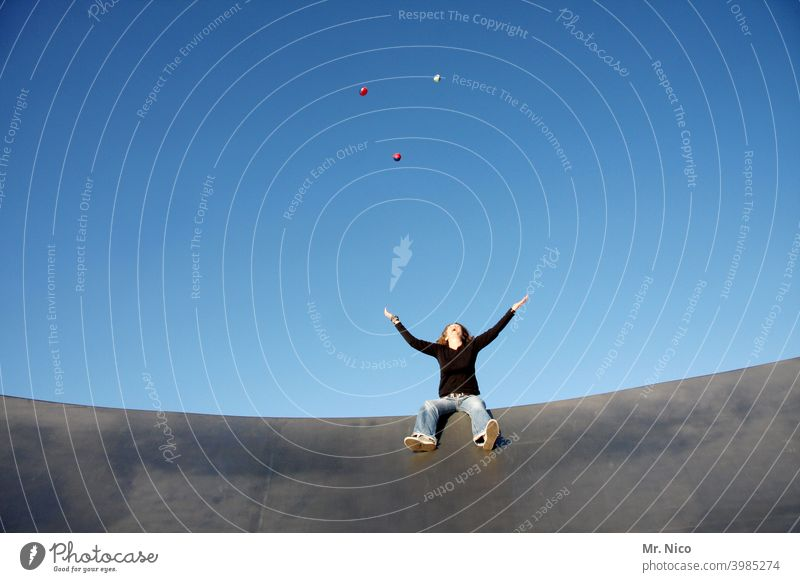 Seated Juggling Juggle Blue sky Playing Leisure and hobbies Throw Ball spread arms Sit Upward Looking Movement Concentrate Throw in the air Acrobatics Heavenly