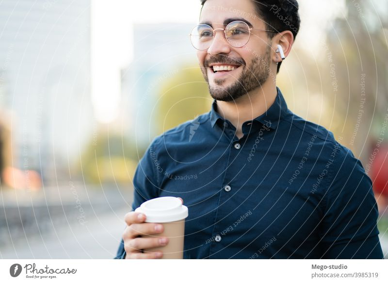 Young man holding a cup of coffee while walking outdoors. portrait young urban take away close up beverage one closeup ear buds leisure ear pods day