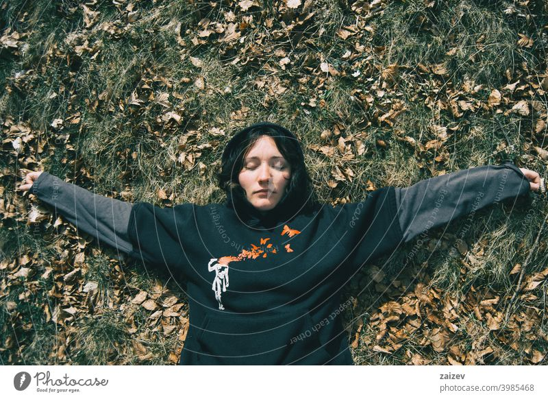A girl with closed eyes lying down resting in nature woman lady young teen ground repose calm calmly quietness silence leaves dry dried natural zen sleep