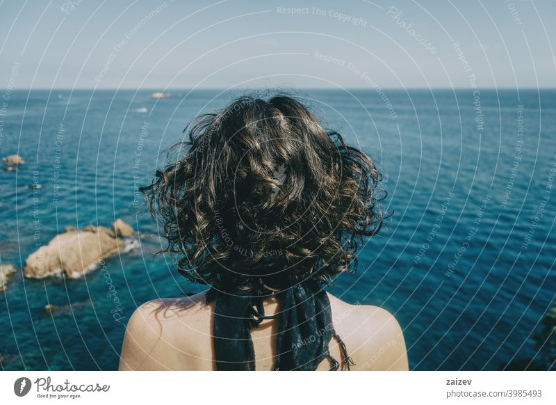 A girl with a kerchief on her neck and her back naked from behind looking at the horizon in the sea costa brava calella de palafrugell palamós woman lady