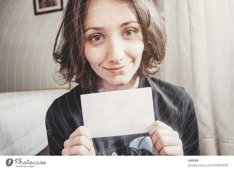 girl smiles while holding a paper with her hands people female one person indoor teen 20s 30s medium copy space center landscape horizontal color blue eyes