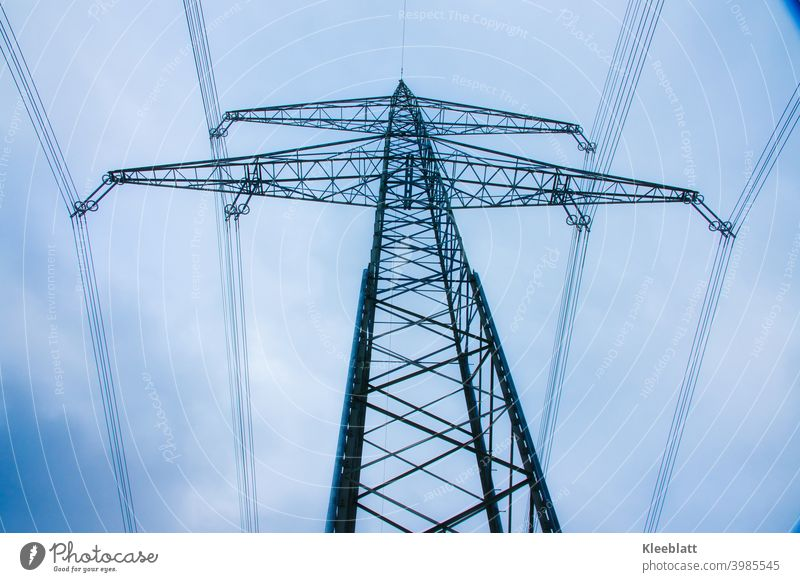 High voltage pylons on blue cloudy winter sky - frog perspective power line high-voltage pylons Worm's-eye view Blue Sky from bottom to top