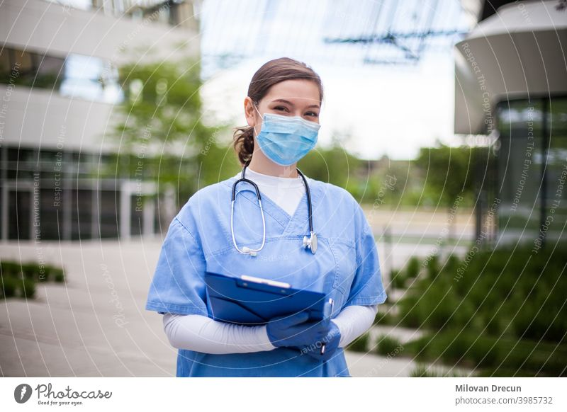 Doctor in front of hospital or nursing home, wearing blue scrubs, face mask, holding clipboard with patient form assisted living building care convalescent