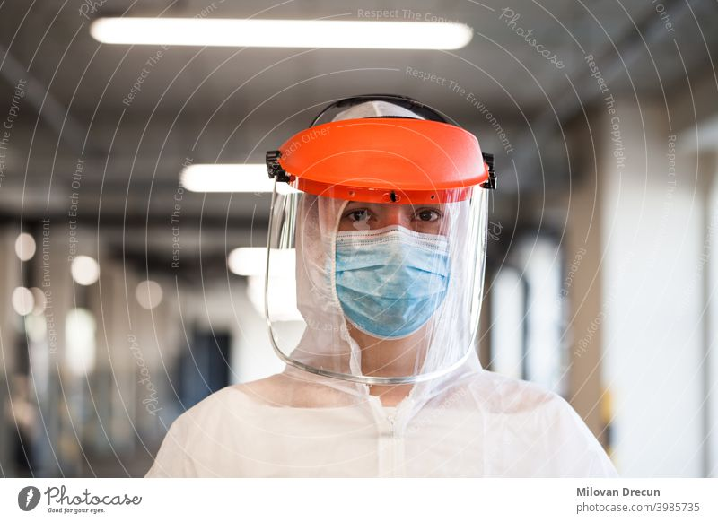 Portrait of female paramedic wearing personal protective equipment, face mask and face shield, standing in a hospital hallway or corridor ambulance background