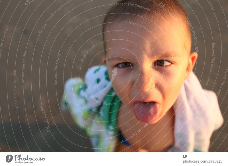 child sticking his tongue out Looking into the camera Portrait photograph Upper body Sunset Sunrise Sunbeam Sunlight Light Structures and shapes Exterior shot