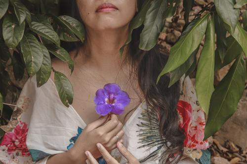 Woman wearing a floral summer dress and holding a flower to her chest, showing concept of mindfulness, meditation, spring season and life new beginnings blossom