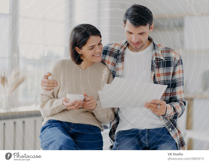 Caring man embraces his wife, look through documents with happy expressions, study payment bills, drinks coffee, dressed in casual wear, pose in spacious room with blurred background. Family and work