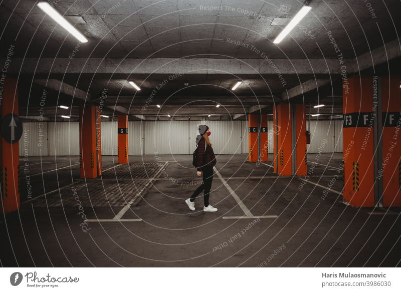 woman with facial mask walking in empty parking garage with neon lights public city coronavirus covid-19 epidemic face mask fashion female girl hat jacket