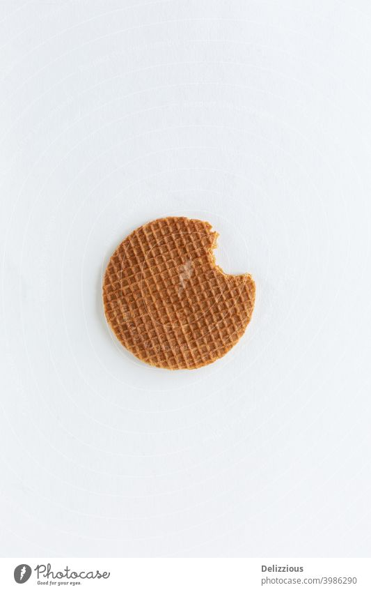 A single Dutch stroopwafel (syrup or caramel waffle) with a bite out of it on white background bake biscuit brown bunch butter circle closeup cookie delicacy