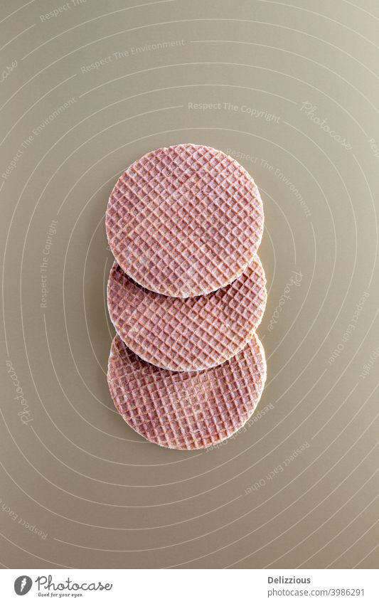 Three traditional Dutch stroopwafels (syrup or caramel waffles) on a golden background, copy space bake biscuit brown bunch butter circle closeup cookie