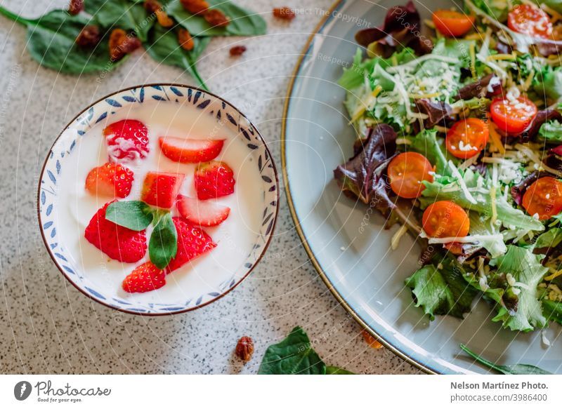 Close-up of a healthy meal of yogurt with strawberries, accompanied by a plate of fresh salad. food lettuce tomatoes cherry tomatoes Food vegetarian Cooking