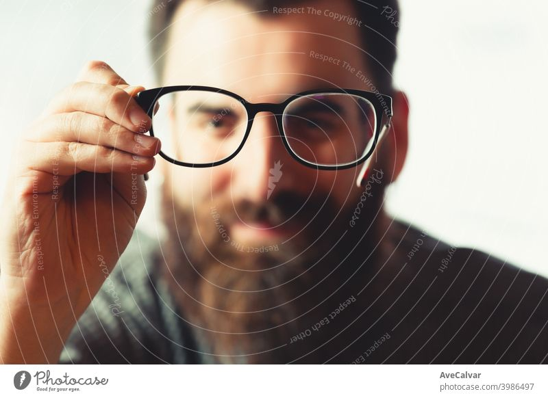 An out of focus hipster male holding a pair of blue light glasses on focus to camera while smiling 20s contemplation entrepreneur genius technology headshot
