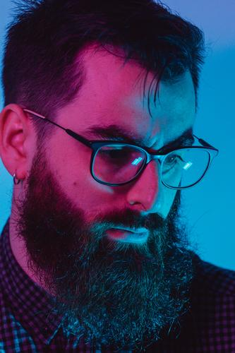A young hipster male with blue light glasses looking away to camera with a serious face on blue and pink colors 20s contemplation entrepreneur genius technology
