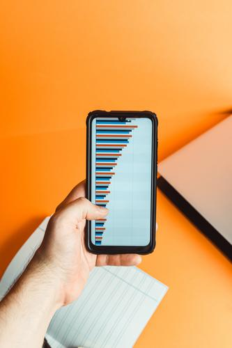 A hand holding a phone with statistics over a orange background with laptop and notebook with financial concept blank business office desk empty keyboard