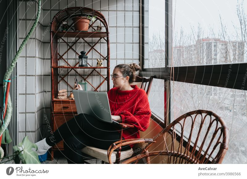 A young woman working on his laptop sitting on a wooden chair on a crystal gallery during a bright day in the city documents horizontal job living relaxed