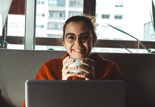 A young woman smiling in front of his laptop in the couch while he holds a cup of coffee Documents Horizontal job living relaxed Research Successful Teacher