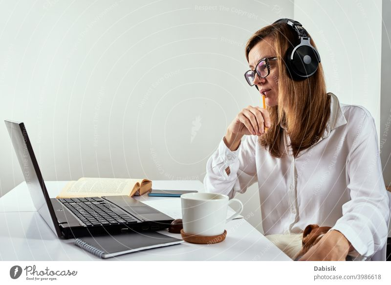 Remote work. Online cources, distance education and e learning concept. Woman in headphones listen audio course at laptop online remote study webinar conference
