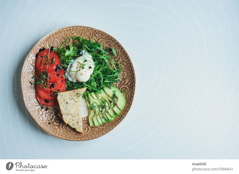 healthy diet vegetarian breakfast - poached egg, whole grain bread, tomatoes, avocado, arugula salad with olive oil and micro green vegetable food lunch meal