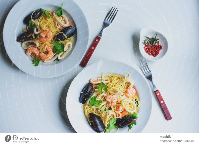 tasty gourmet spicy seafood pasta with shrimps, squid and mussels cooked with pink pepper and thyme spaghetti plate meal dinner lunch noodle dish healthy tomato