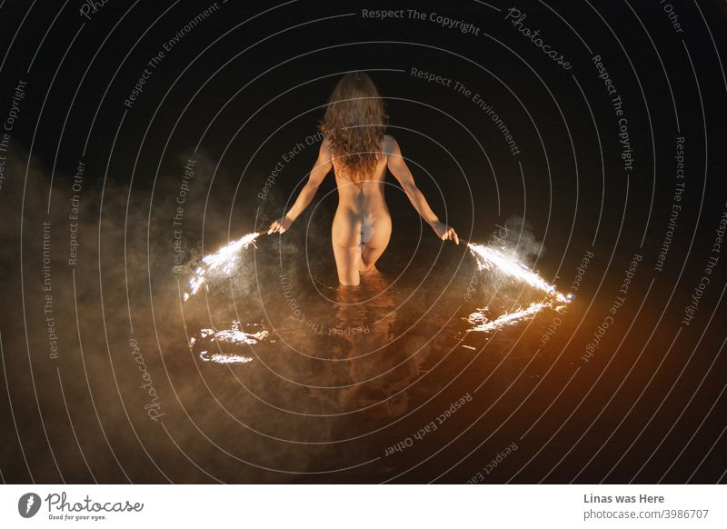 Wild and naked girl is swimming at night. Erotic image of a brunette model. Fireworks in her hands, sexy back show her perfect curves, smoke, and dark water makes this scene moody and sensual.
