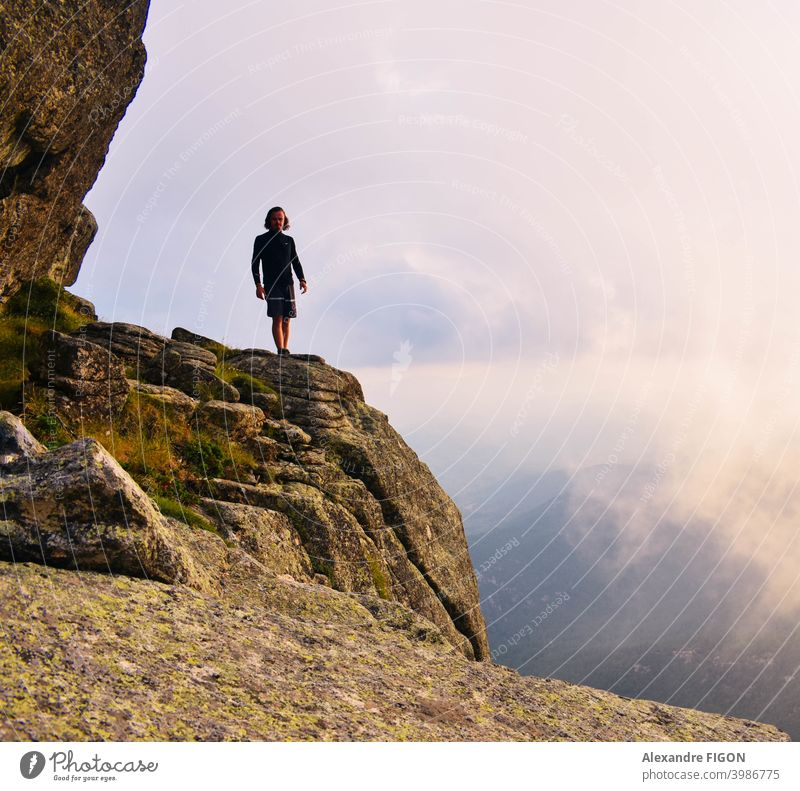 A man standing at clouds heights in the mountains next to a canyon Mountain summit hike sunset rocks colorful Height Panorama (View) Nature Landscape Sky Day